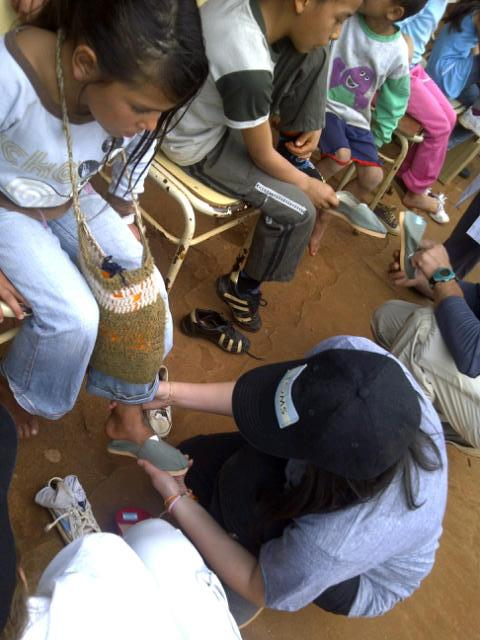 Gowalla / AT&T Contest winner Mina fits TOMS Shoes on a child in San Pedro Province, Argentina